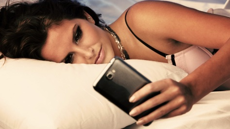 Sleepy-woman-checking-messages-on-cell-phone